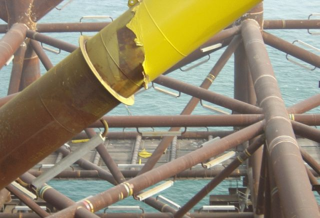 "Sacrificial anodes (light colored rectangular handle-shaped objects) mounted ""on the fly"" for corrosion protection of a metal jacket structure. Photo credit: Wikimedia Commons/CC-BY-SA-2.5"